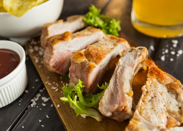 Alto angolo di bistecca con insalata e birra Foto Gratuite