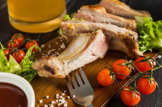 Alto angolo di bistecca con pomodori e birra Foto Gratuite