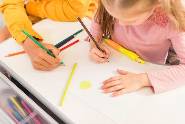 Учитель под высоким углом помогает ученику в классе Бесплатные Фотографии