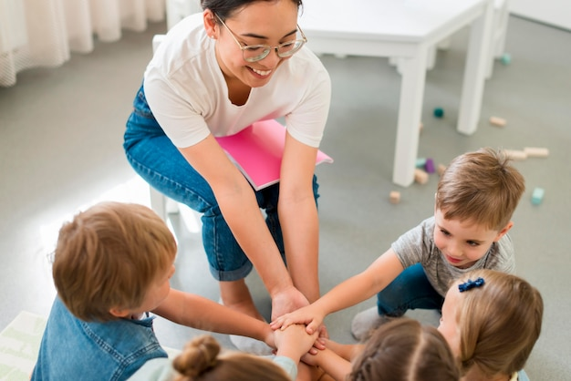 幼稚園で生徒と遊ぶハイアングル教師 Premium写真