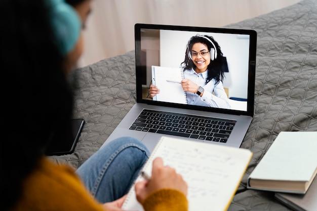 Elevato angolo di adolescente utilizzando laptop per la scuola in linea Foto Gratuite