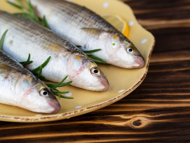 Высокий угол три рыбы на тарелку с травами Бесплатные Фотографии
