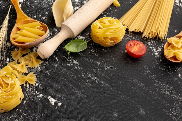 High angle uncooked pasta with rolling pin and copy space Free Photo