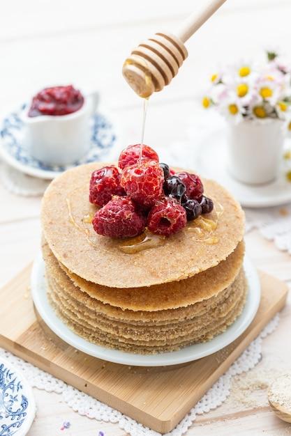 蜂蜜とベリーと生のビーガンパンケーキの高角度の垂直クローズアップショット 無料写真