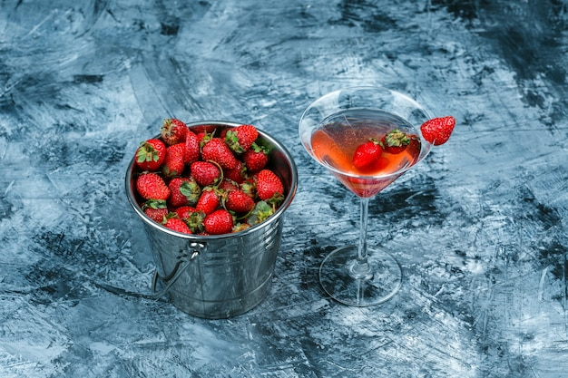ハイアングルビューダークブルーの大理石の表面にイチゴのバスケットとイチゴカクテルのグラス。水平 無料写真