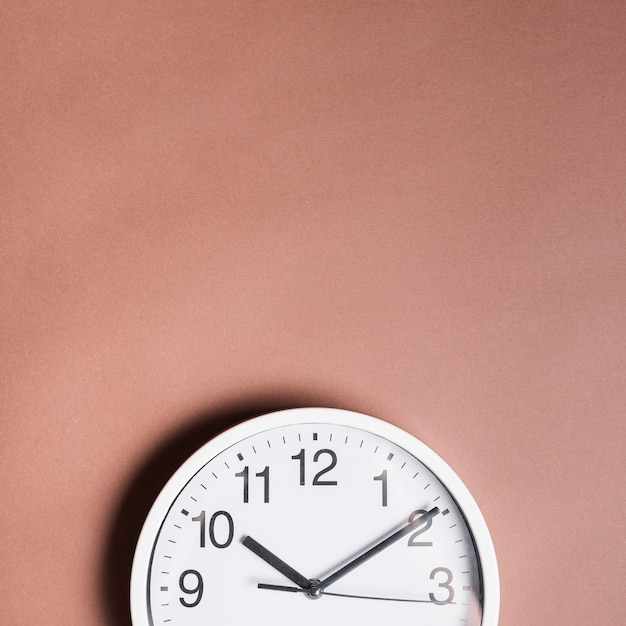 High angle view of an alarm clock on brown backdrop Free Photo