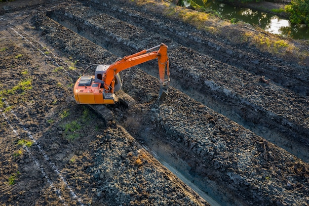 High angle view backhoe is dingging the groove garden and agricultural area thailand Premium Photo