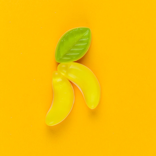 High angle view of banana candies on yellow backdrop Free Photo