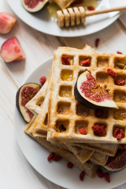 High angle view of belgian waffles; honey with fig fruit in plate Free Photo