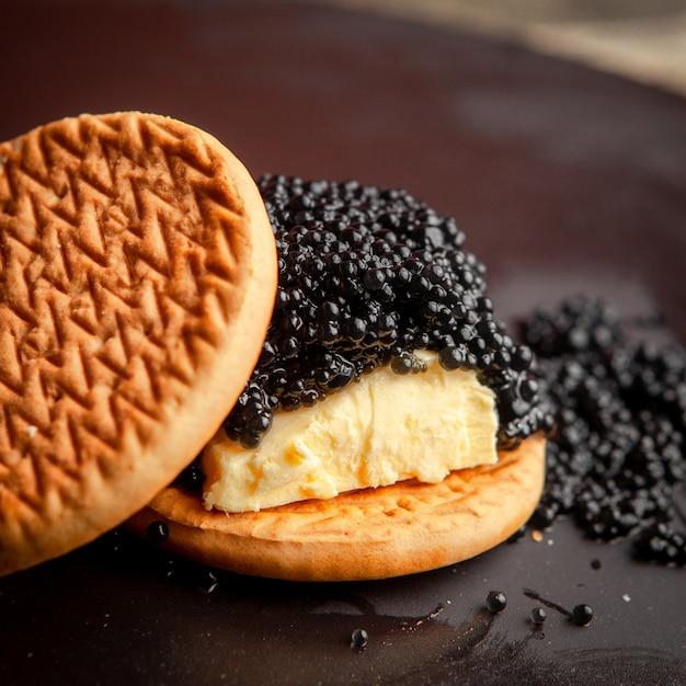 Caviale nero di vista dell'angolo alto fra i biscotti con burro su fondo scuro. Foto Gratuite