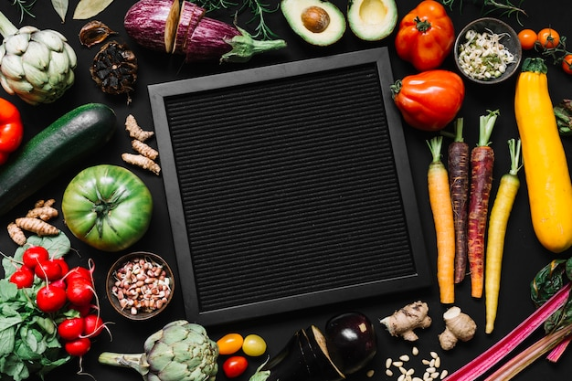 High angle view of black frame surrounded with various raw vegetables Free Photo