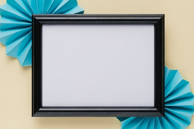 High angle view of black wooden border photo frame with blue origami fan on beige background Free Photo