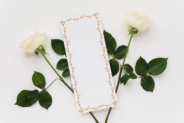 High angle view of blank card with two roses on white background Free Photo