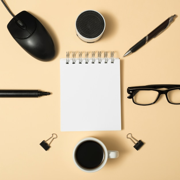 High angle view of blank spiral notepad surrounded by bluetooth speaker; pen; paper clips; coffee cup; eyeglass on beige background Free Photo