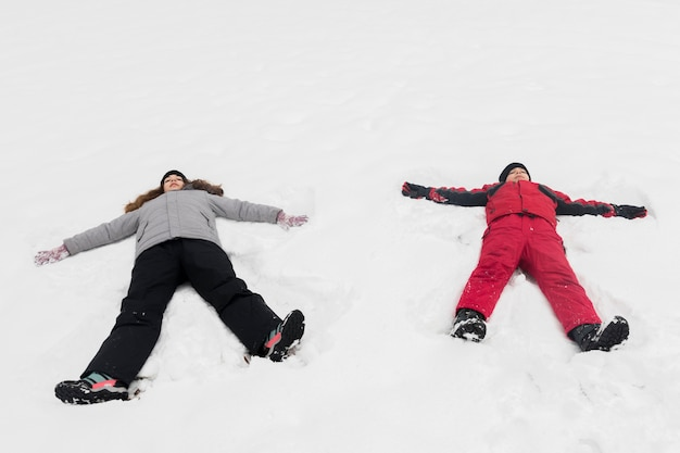 High angle view of brother and sister lying on snow Free Photo