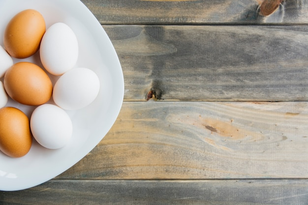 High angle view of brown and white eggs on plate on wooden surface Free Photo