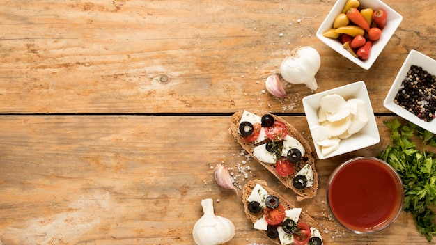High angle view of bruschetta and ingredient on wooden background Free Photo