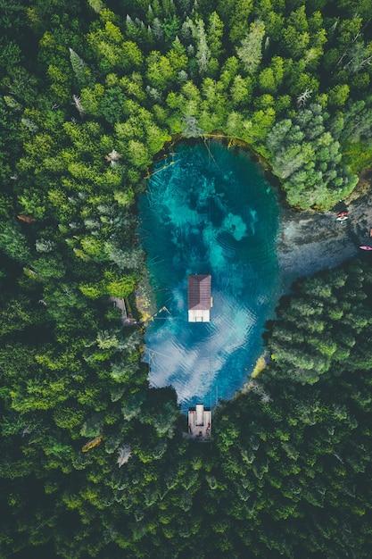 Veduta dall'alto di un edificio in un lago circondato da boschi sotto un cielo nuvoloso Foto Gratuite