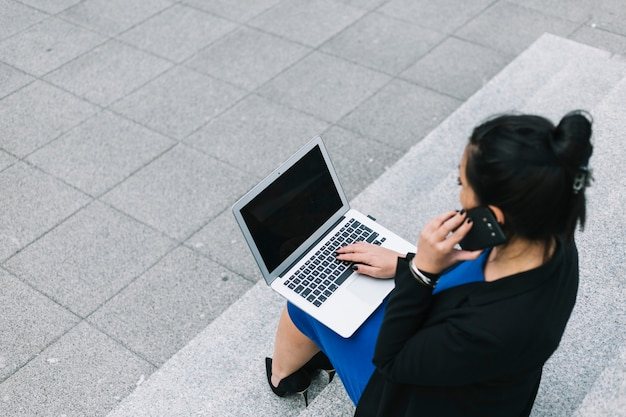 High angle view of businesswoman using laptop and talking on mobile phone Free Photo