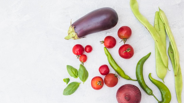High angle view of cherry tomatoes; hyacinth beans; basil; onion and green chili peppers on white backdrop Free Photo