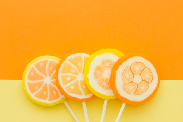 High angle view of citrus fruit candies on yellow and orange background Free Photo