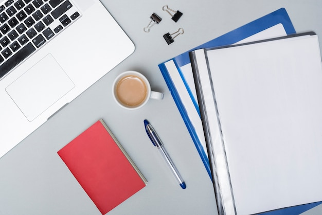 High angle view of coffee cup; laptop; folders and paper clips with laptop on gray background Free Photo
