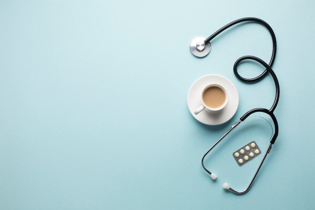 High angle view of coffee cup; stethoscope and medicine in blister pack over blue backdrop Free Photo