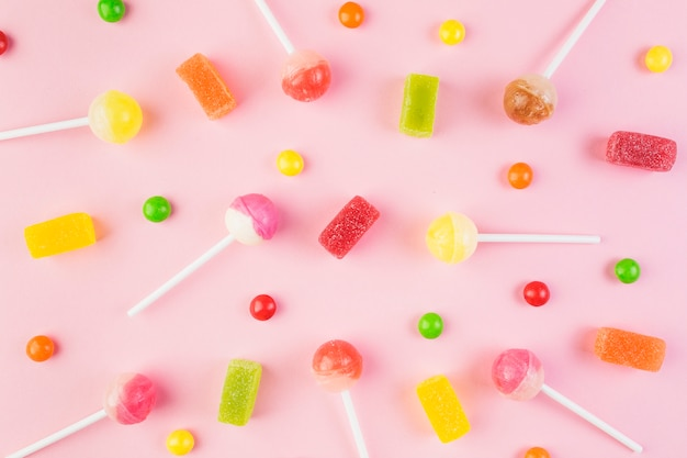 High angle view of colorful candies and lollipops on pink surface Free Photo
