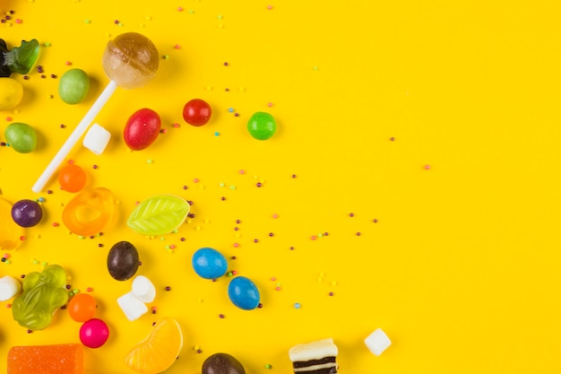 High angle view of colorful candies and lollipops on yellow backdrop Free Photo