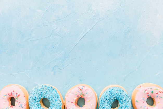 High angle view of colorful donuts at the bottom of blue background Free Photo