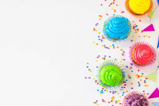 High angle view of colorful muffins and candies on white backdrop Free Photo