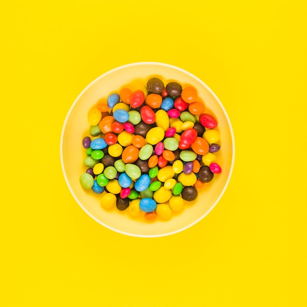 High angle view of colorful sweet candies on plate over yellow surface Free Photo