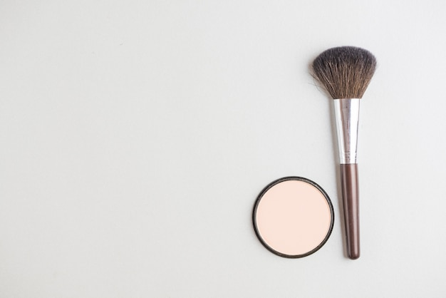 High angle view of cosmetic powder and brush on white backdrop Free Photo