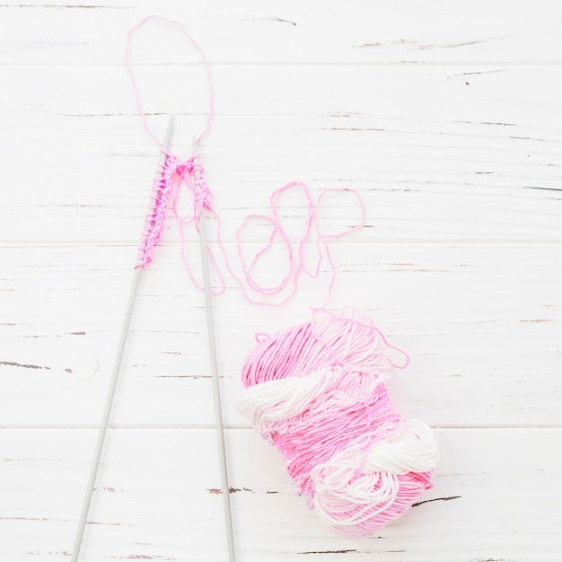 High angle view of crochet with pink yarn on wooden background Free Photo