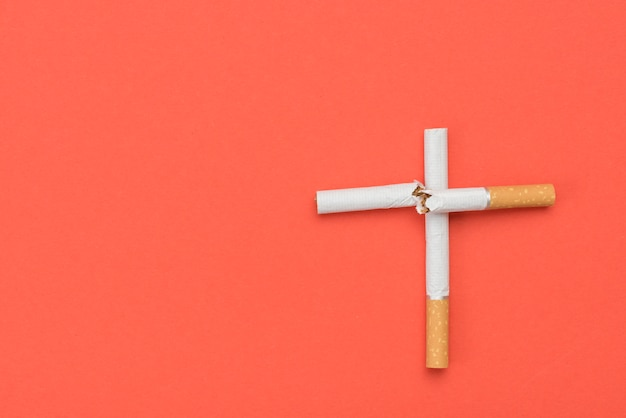 High angle view of cross sign made from cigarette on orange background Free Photo