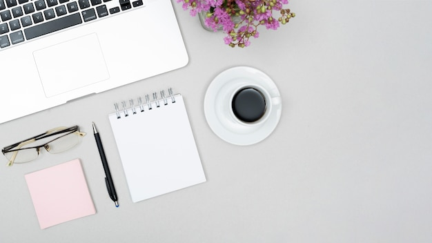 High angle view of cup of coffee; laptop; eyeglass; spiral note pad flower pot on gray table Free Photo