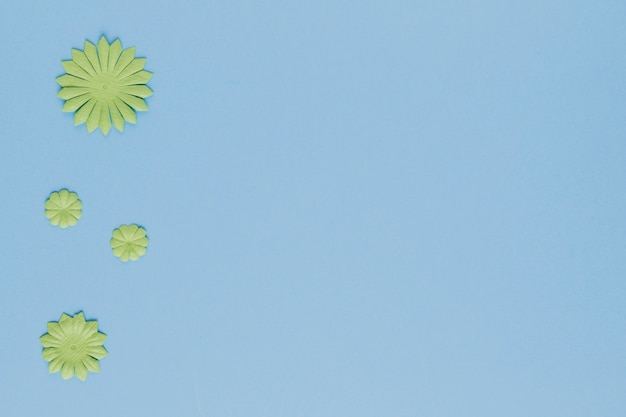 High angle view of decorative green flower cutout on blue background Free Photo