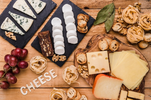 High angle view of delicious fresh food with cheese text on wooden surface Free Photo