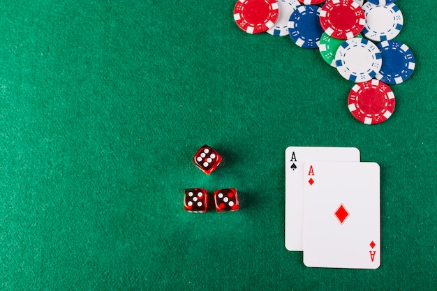 High angle view of dice; chips and ace playing cards on poker table Free Photo