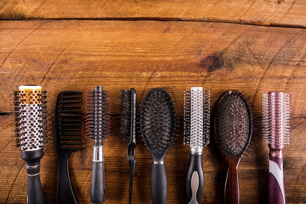 High angle view of different hairbrushes on wooden backdrop Free Photo