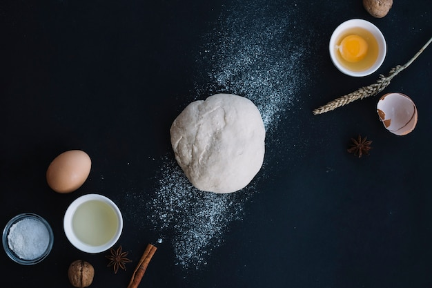 High angle view of dough with baking ingredients on black backdrop Free Photo