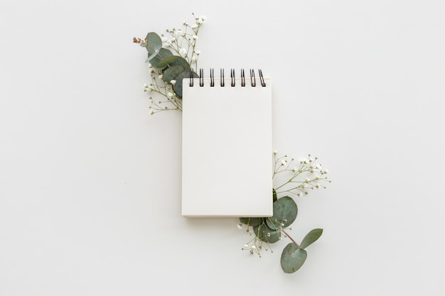 High angle view of empty spiral notepad with leafs and baby's breath flowers on white surface Free Photo