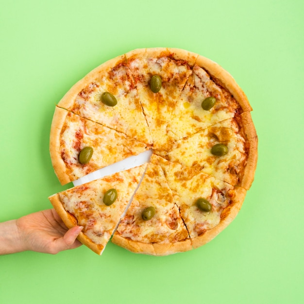 High angle view of female hand holding pizza slice over green background Free Photo