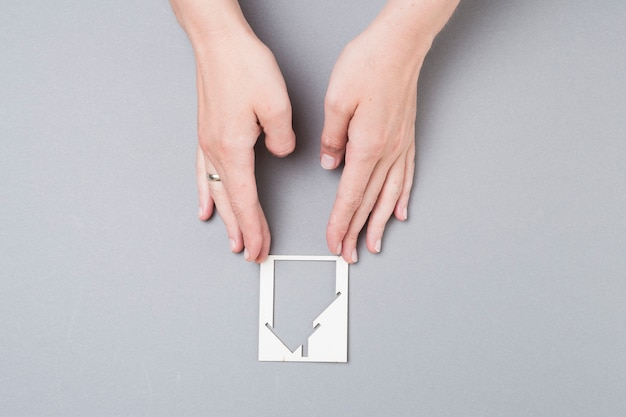 High angle view of female hand touching house cutout on grey background Free Photo