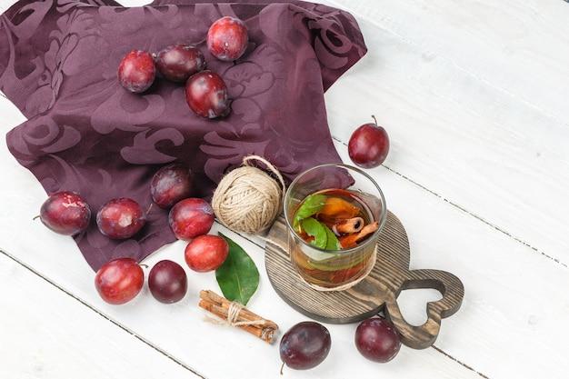 白い木の板の表面にシナモン、クルー、バーガンディのテーブルクロスを備えたハイアングルビュー発酵飲料。水平 無料写真