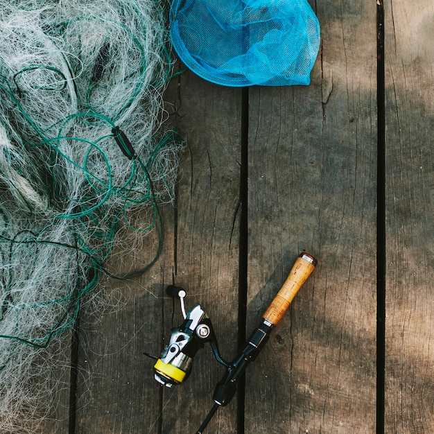 High angle view of fishing rod and net on wooden plank Free Photo