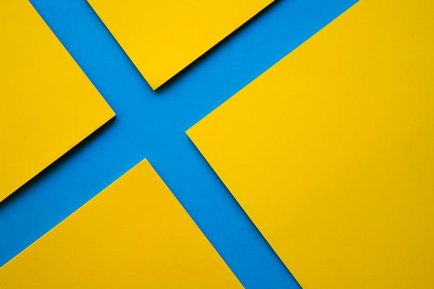 Una vista di alto angolo di quattro carte gialle del mestiere sulla superficie del blu Foto Gratuite