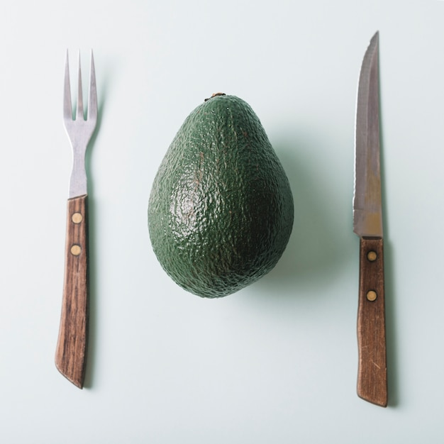 High angle view of fresh avocado; knife and fork on green surface Free Photo