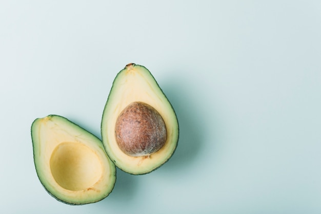 High angle view of fresh halved avocado on green surface Free Photo