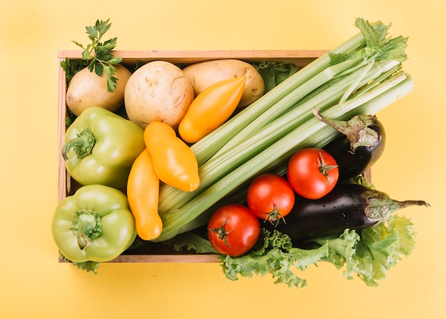 High angle view of fresh vegetables in container over yellow background Free Photo